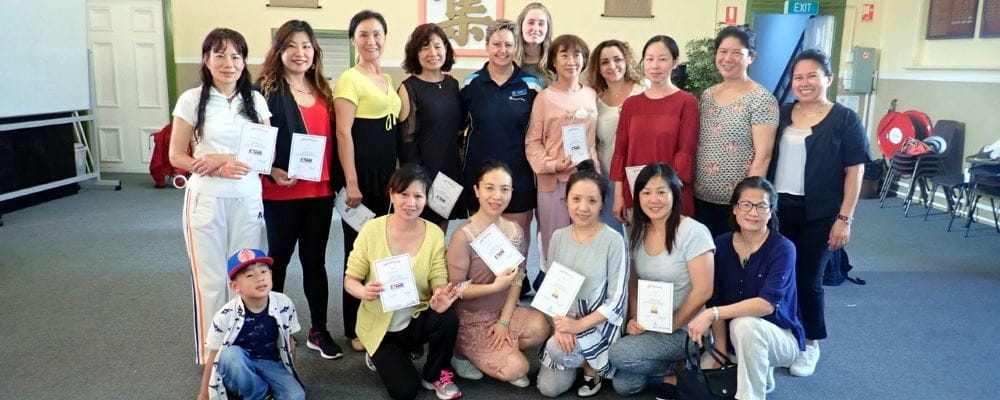 A group of Chinese women with their trainer holding their certificates after completing a Heart Beat Club course