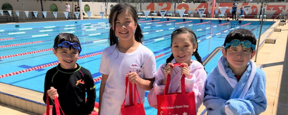 Four children stadning by the pool at Churchlands with their Swim and Survive packs