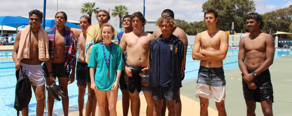 A group of boys from the Clontarf Academy in Geraldton pose by the pool