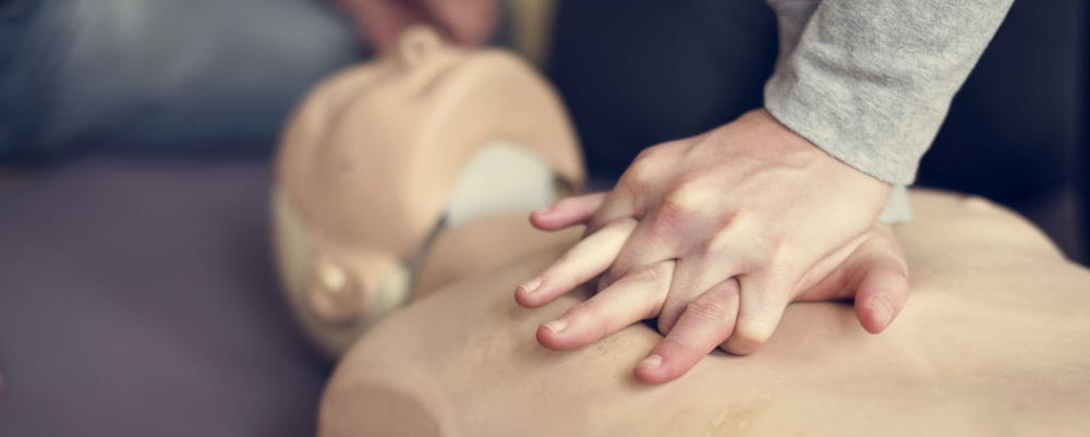 A person prasticing CPR on a manikin