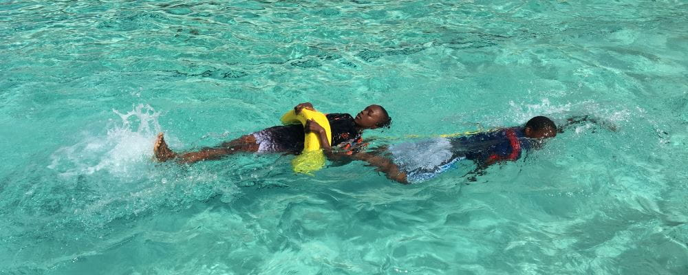 two boys lifesaving in the pool