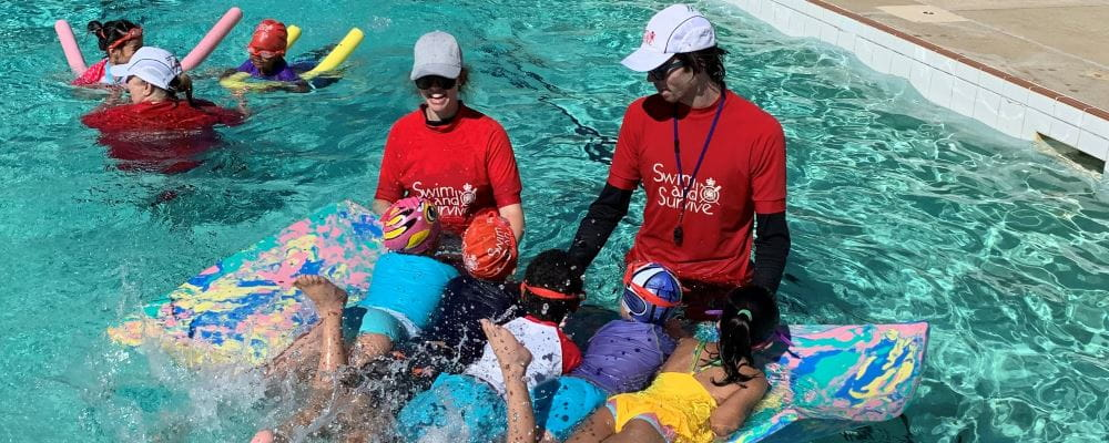 Swim instructors with multicultural children in the water having fun at Dianella