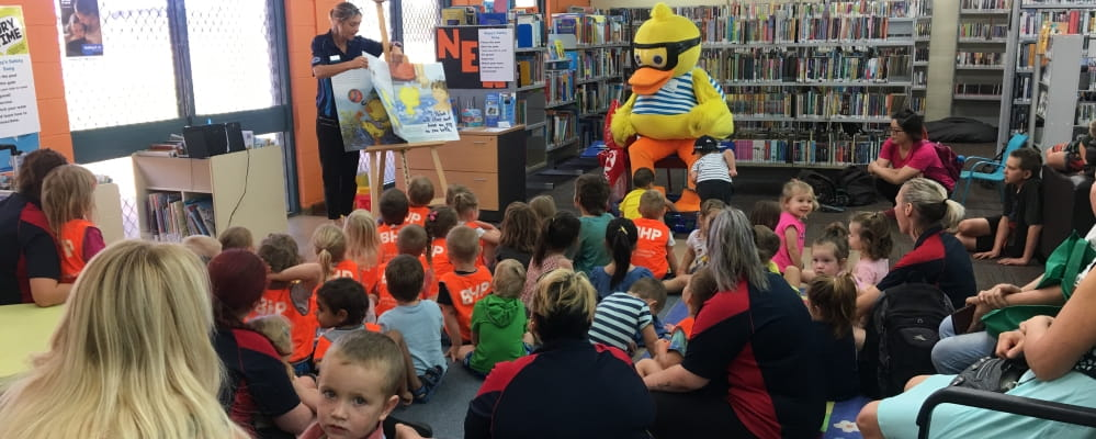Dippy Duck reads a story book to a large group of young kids in a Port Hedland library