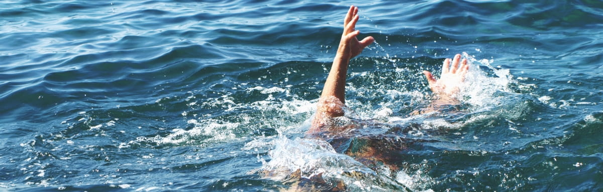 The arm of a drowning victim flails in the water