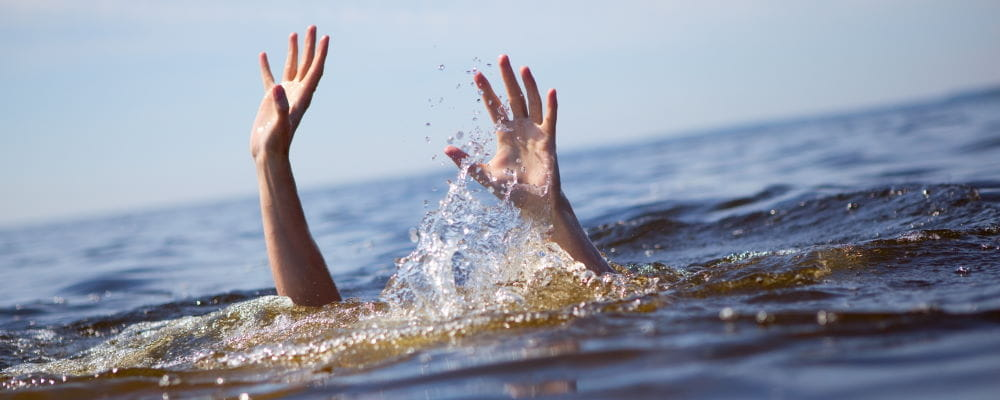 A person underwater with their hands raised above the surface