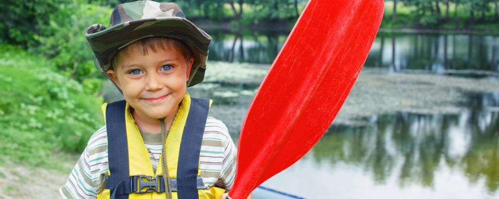 image of small boy wearing lifejacket and holding an oar by the river