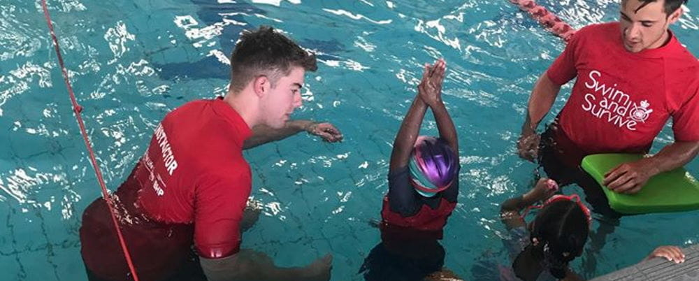 Two swim instructors in the water with two children