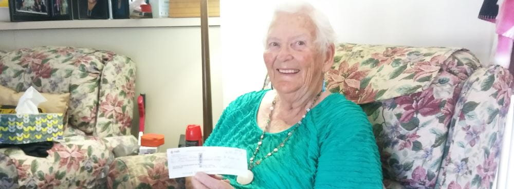Image of winner Phyllis holding her winner's cheque
