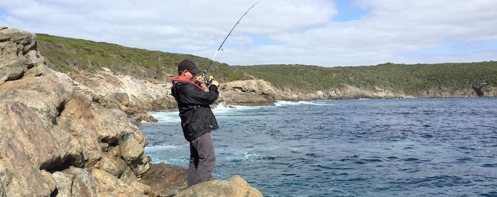 image of man fishing from rocks by ocean