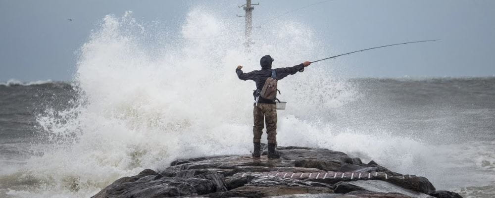 man fishing from rock with ocean wave breaking in front