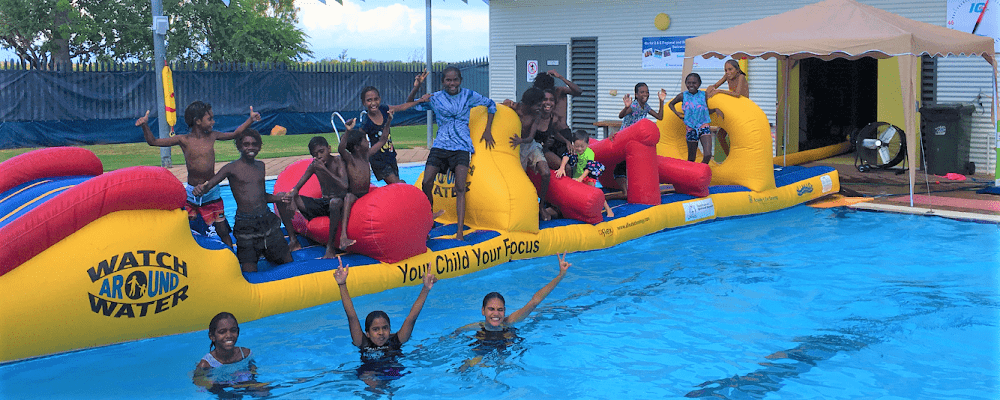 Local kids having fun on a giant pool inflatable at the Fitzroy Crossing pool