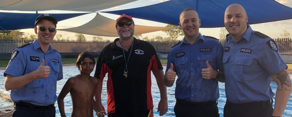 Police officers with a local Aboriginal boy and Pool Manager Trevor Caporn by the Fitzroy Remote Pool