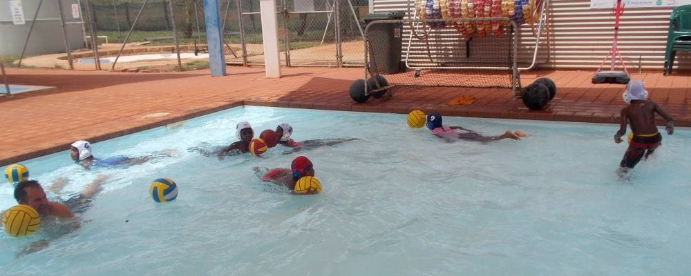children playing flippa ball in the shallow pool at Yandeyarra