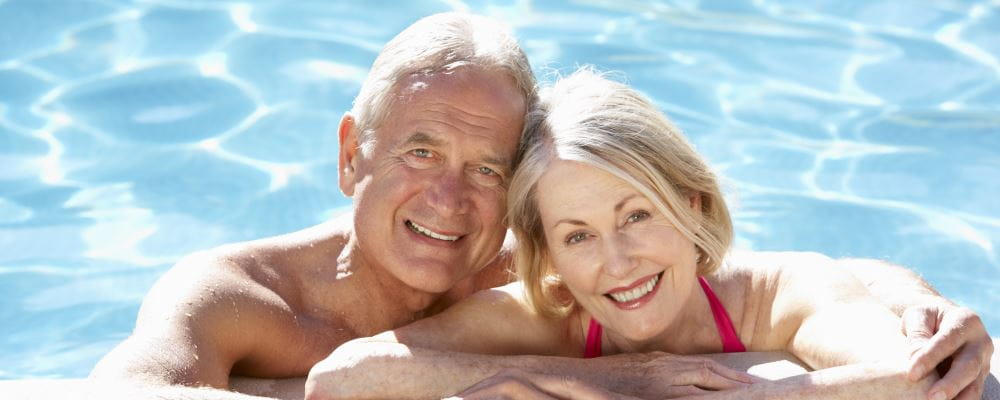A man and woman leaning on the edge of a pool smiling at the camera