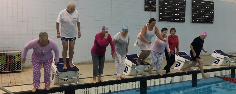 nine senior women jumping into a public swimming pool