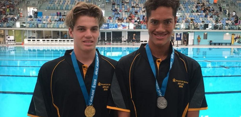 Harrison Hynes and TJ CHong Sue by the pool with their medals in Adelaide