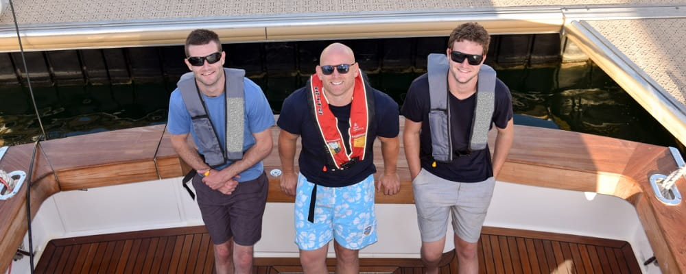 three men wearing lifejackets standing on the back of a boat looking up at camera