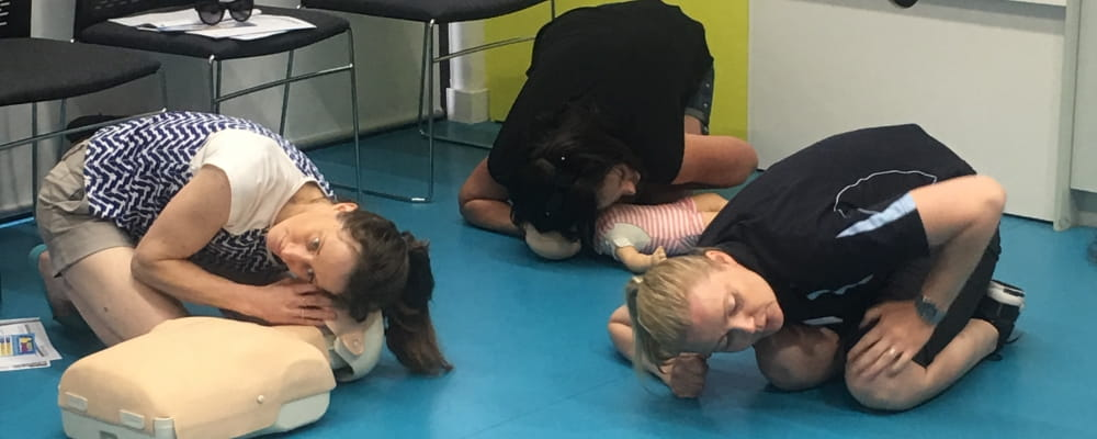 Parents practising CPR skills during a Heart Beat Club session