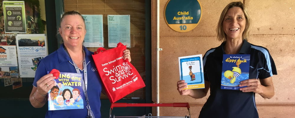 Two women holding Royal Life Saving books and activity bags