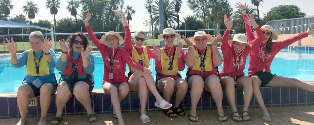 Eight swim instructors sitting by the pool with arms in the air at South Hedland Aquatic Centre