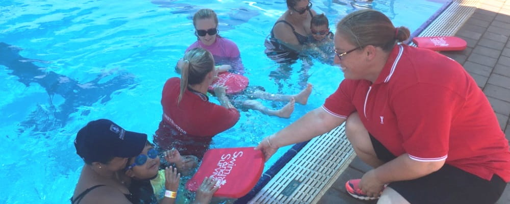 image of raelene leeds handing a swim and survive kick board to a participant in an infant aquatics class