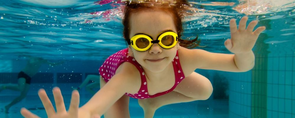 image of girl underwater in a pool looking at camera