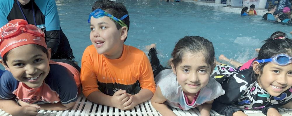Four Islamic children leaning on the edge of the pool during their swimming lesson, smiling