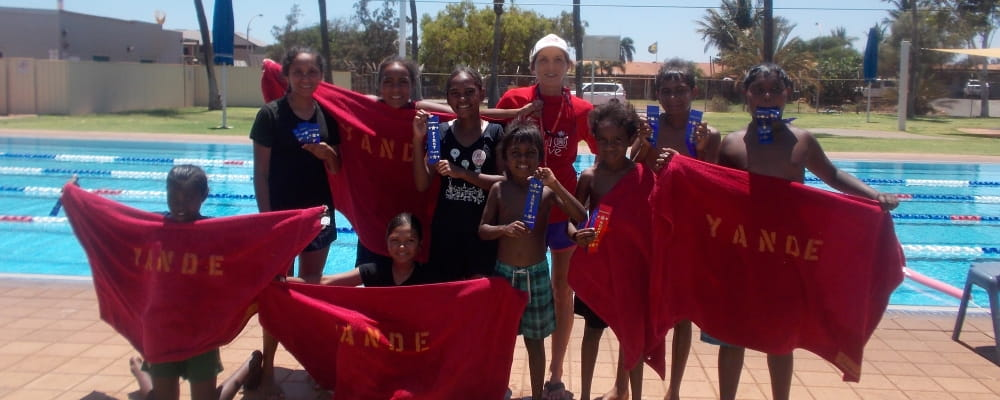 A group of kids from Yandeyarra pool surround Pool Manager Jacqui Forbes