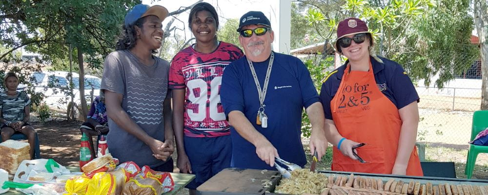 Jigalong Pool Manager David Lucas cooking sausages on the barbeque with two aboriginal youths and a woman looking on
