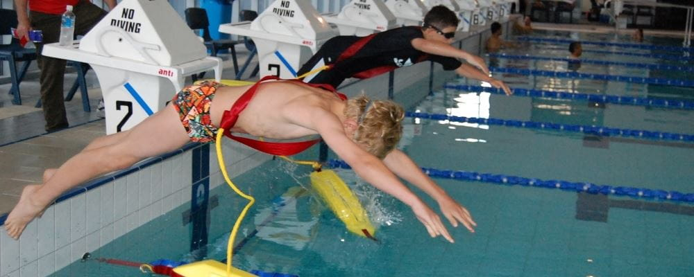Image of young boy diving into pool with rescue tube