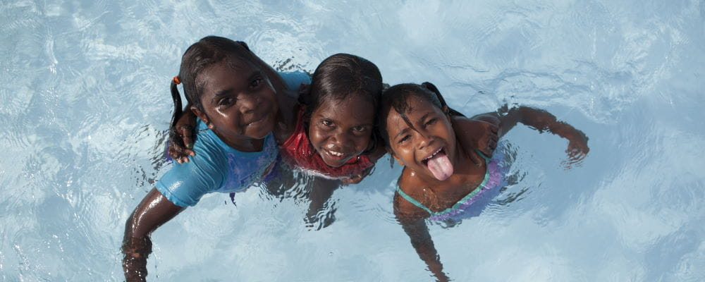 Three aboriginal girls in a swimming pool smiling at the camera