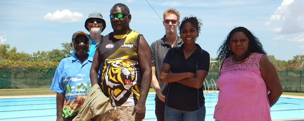 Kulumburu representatives Clement Maraltadj (Kalumburu Chairperson), Derick Charles, Kimberley French and Margaret Clement, with Warmun Pool Manager Jamie O'Donohue and RLSSWA's Greg Tate by the swimming pool at Warmun