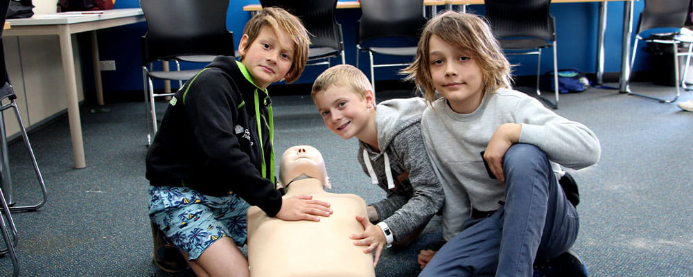 Three young boys practising CPR on a manikin