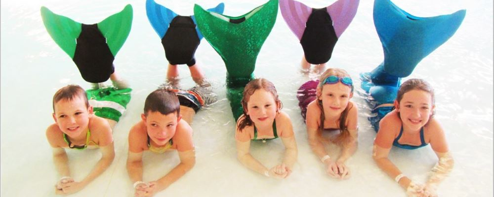 two boys and 3 girls wearing mermaid tails and monofins laying in the water smiling at camera
