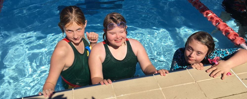 Three girls in the pool at the ACC Inclusion Swimming Carnival