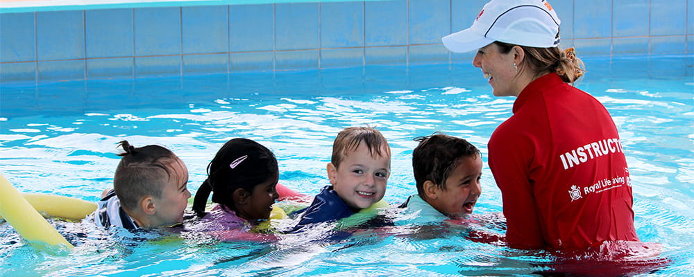 Four children with their swim instructor in the pool on pool noodles
