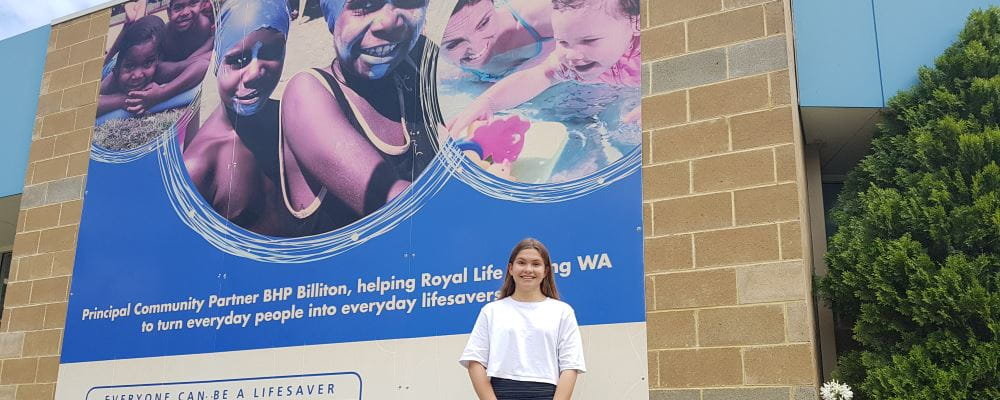 Lily Symons by the sign on the Royal Life Saving building that features her as a baby