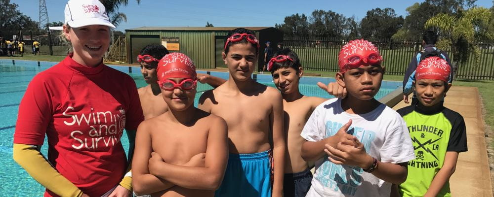 A swim and Survive instructor standing with 6 multicultural boys by the pool at Lynwood