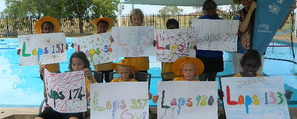 Children hold up signs with number of laps swum