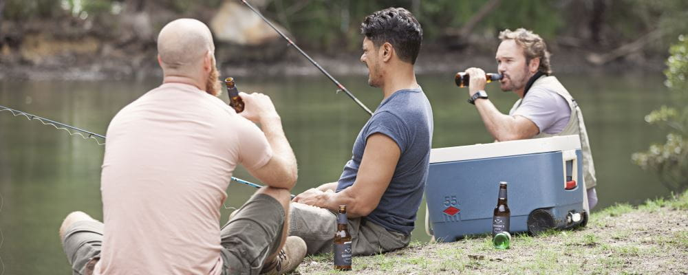 Three men by the river drinking alcohol