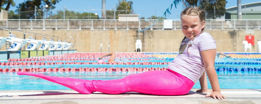 A young girl wearing a pink mermaid tail by the pool