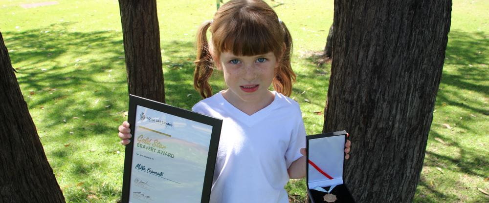 Milla Fearnall with her Bravery Award certificate and medal
