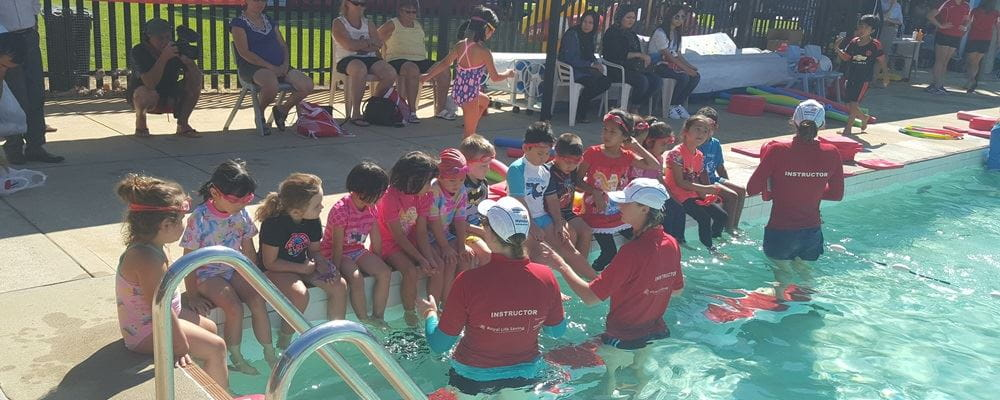 multicultural children sitting on the edge of the pool with 3 instructors ready to start a lesson