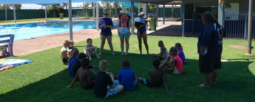 Swim instructors talking to children sitting on grass by the pool at Mount Magnet