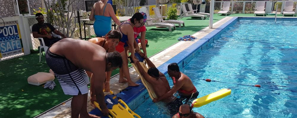 Lifeguards by the pool in Oman using spineboards to remove people from the water