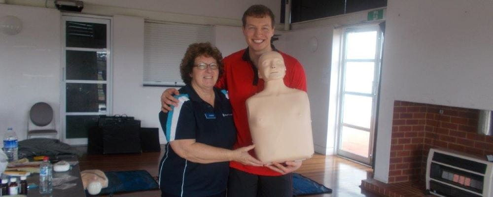 Royal Life Saving community trainer Marion, with Sam Kempton from YMCA holding a CPR manikin