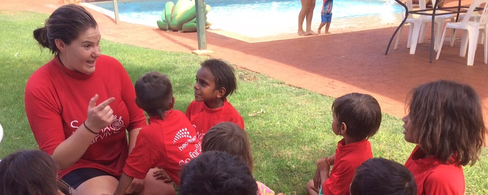 Aboriginal children wearing red Swim and Survive rashies with their instructor on the grass at the Newman Aquatic  Centre