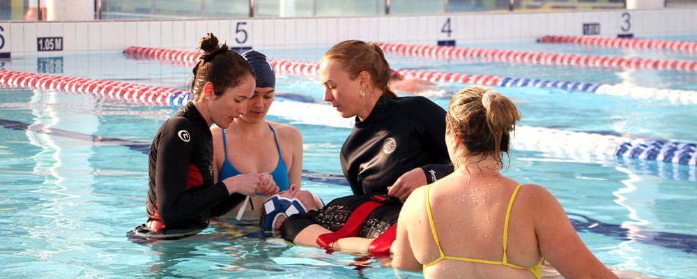 Pool Lifeguard in the water practising spinal procedures