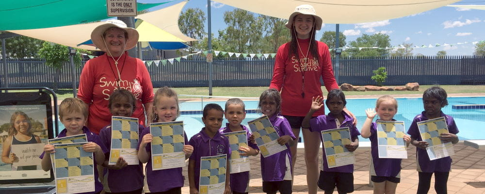 Adele Caporn and Niamh Hurley with Fitzroy Crossing children holding their swimming certificates