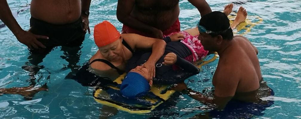 a mal and female lifeguard holding a colleague on a spineboard in the pool as they practise their skills
